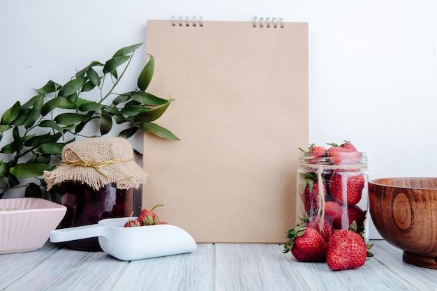 Zijaanzicht van een schetsboek met aardbeienjam in een glazen pot en verse rijpe aardbeien in een glazen pot op rustieke