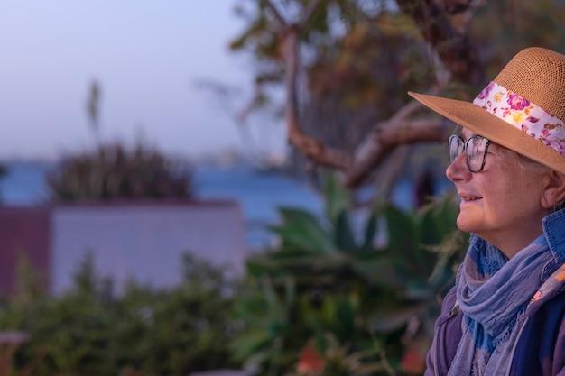 Zijaanzicht van een senior vrouw met een hoed zitten in de buurt van het strand kijkend naar de horizon en bij zonsondergang. serene levensstijl voor gepensioneerden.