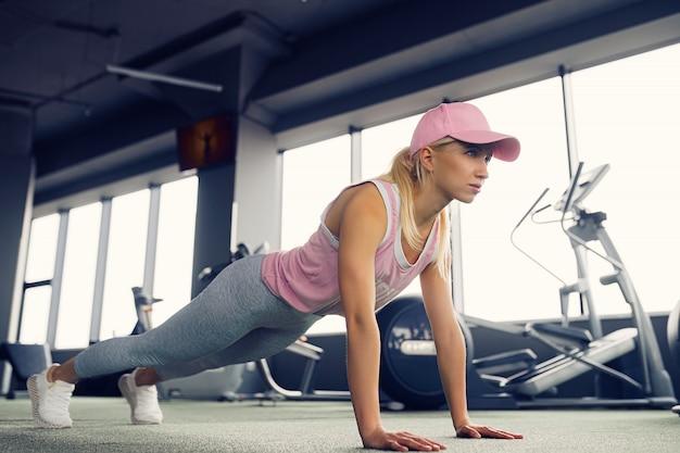 Zijaanzicht van een slank fitnes jong blondemeisje die planking oefening doen bij gymnastiek.