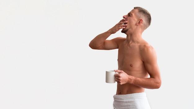 Zijaanzicht van een slaperige shirtless man in de ochtend met koffie