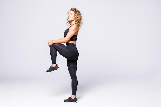 Zijaanzicht van een sportieve jonge fitness vrouw springen geïsoleerd op een witte muur