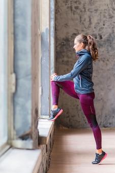 Zijaanzicht van een sportieve jonge vrouw die door venster kijkt
