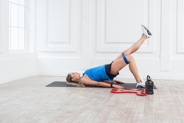 Zijaanzicht van een sterke en fitte atletische jonge blanke vrouw in sportkleding met banden die benen trainen en gespierde billen. fitness trainen met expander. indoor, studio-opname, sport en gezond concept