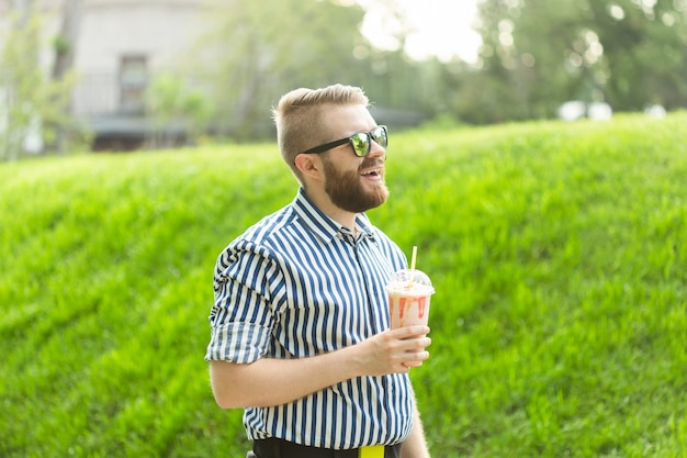 Zijaanzicht van een stijlvolle jonge man met een baard die een milkshake vasthoudt en het uitzicht op de stad bewondert