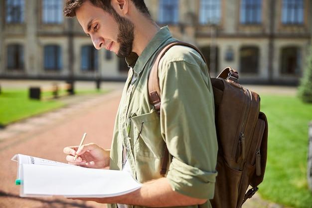 Zijaanzicht van een student die met een potlood in zijn hand naar een werkboek staart