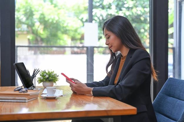 Zijaanzicht van een succesvolle zakenvrouw die voor een computertablet zit en haar mobiele telefoon controleert.