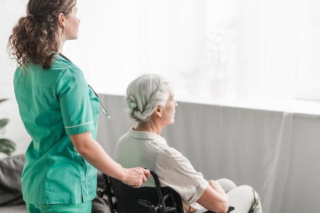 Zijaanzicht van een verpleegster die gehandicapte patiënt op wielstoel duwen