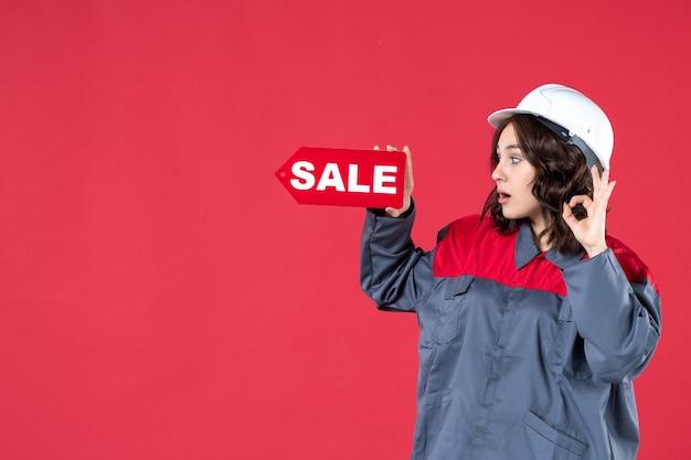 Zijaanzicht van een verraste vrouwelijke werknemer in uniform die een harde hoed draagt en een verkooppictogram aanwijst dat een brilgebaar maakt op geïsoleerde rode achtergrond