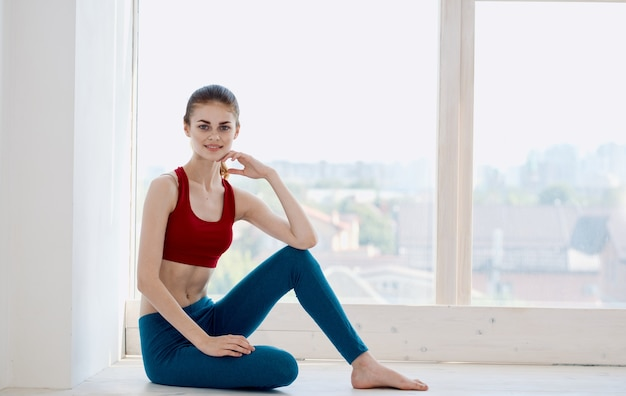 Zijaanzicht van een vreemde vrouw bij het raam binnenshuis in sportkleding