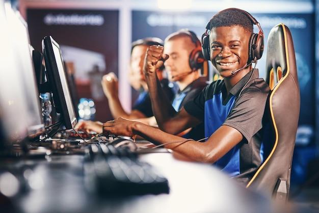 Zijaanzicht van een vrolijke afrikaanse man, professionele cybersport-gamer die een koptelefoon draagt en kijkt naar