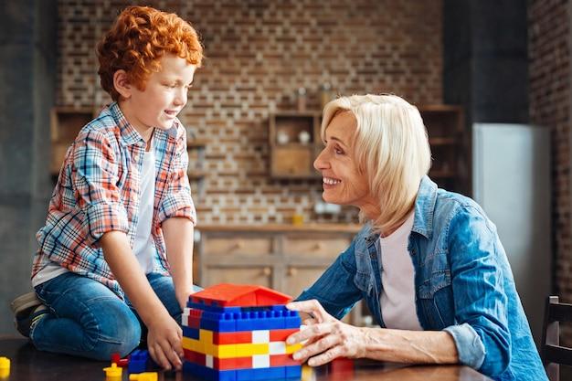 Zijaanzicht van een vrolijke senior dame die lacht en naar haar kleinzoon met gekrulde haren kijkt met ogen vol liefde na het spelen met een bouwdoos en het bouwen van een droomhuis.