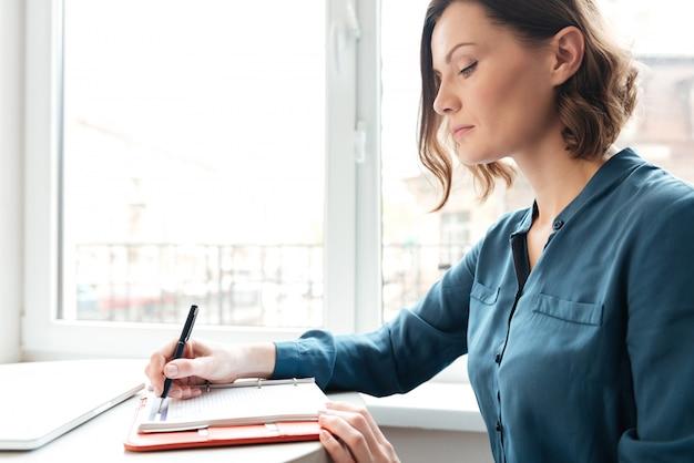 Zijaanzicht van een vrouw die aantekeningen maakt in haar agenda