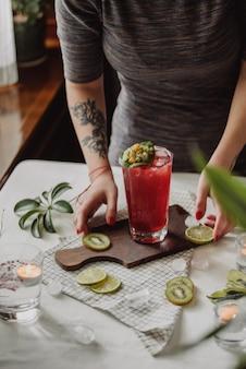Zijaanzicht van een vrouw die een houten bord met aardbeien cocktail en gesneden kiwi op het