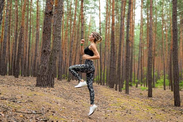 Zijaanzicht van een vrouw die in sportkleding in pijnboompark springt.