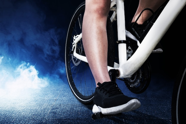 Zijaanzicht van een vrouw die op een fiets rijdt met een lichte achtergrond