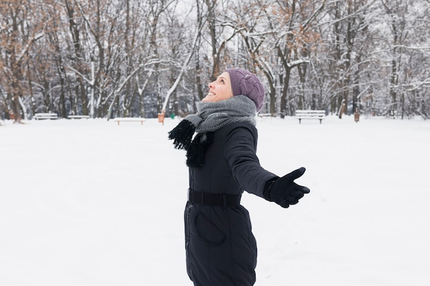 Zijaanzicht van een vrouw die warme kleding draagt die de winter van dag geniet
