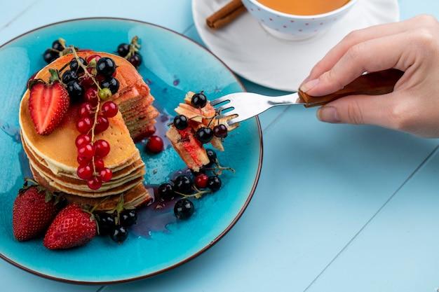 Zijaanzicht van een vrouw eet pannenkoeken met aardbeien, rode en zwarte bessen en een kopje thee op een blauwe ondergrond