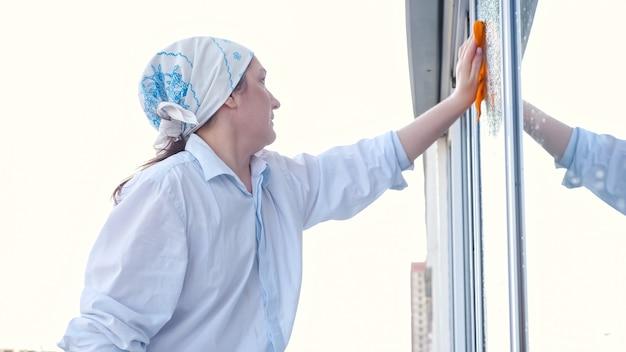 Zijaanzicht van een vrouw in een sjaal wast het raam met een doek.