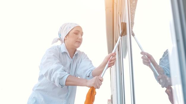 Zijaanzicht van een vrouw in een sjaal wast het raam met een rubberen schraper, zonlicht