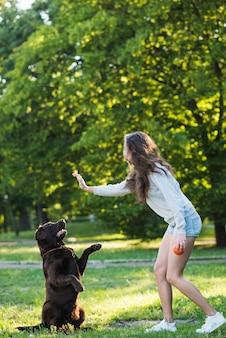 Zijaanzicht van een vrouw met plezier met haar hond in de tuin