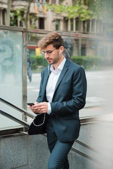 Zijaanzicht van een zakenman die mobiele telefoon met zijn oortelefoon in oren met behulp van