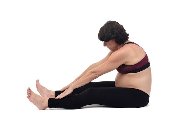 Zijaanzicht van een zwangere vrouw die vloeroefeningen doet op een witte achtergrond