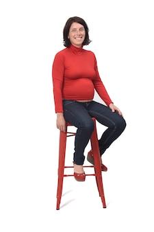 Zijaanzicht van een zwangere vrouwenzitting op een kruk op witte achtergrond