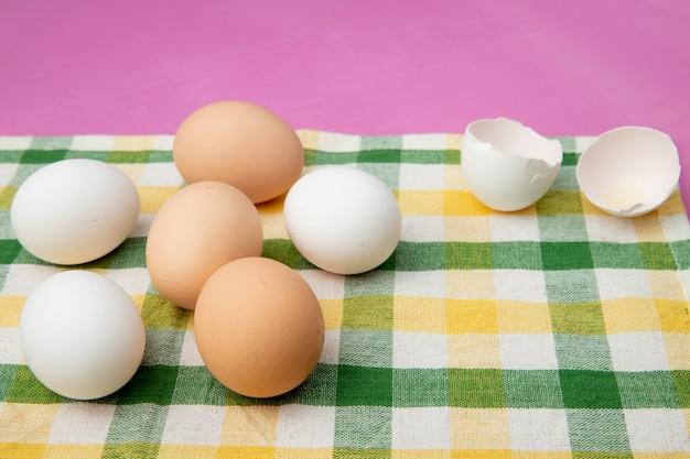 Zijaanzicht van eieren met eierschaal op doek oppervlak en paarse achtergrond