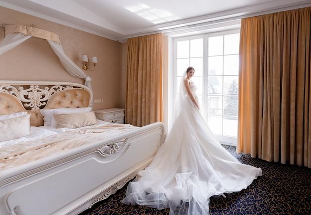 Zijaanzicht van elegante bruid staat bij het raam van een hotelkamer en kijkt in de camera