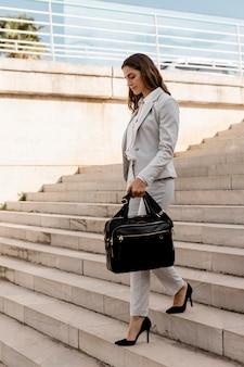 Zijaanzicht van elegante zakenvrouw op trappen buiten met tas
