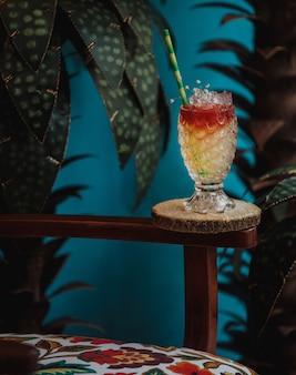 Zijaanzicht van exotische cocktail in reliëf glas in een houten stand op groene muur