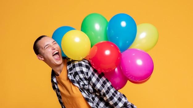 Zijaanzicht van extatische vrouw met ballonnen