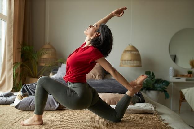Zijaanzicht van flexibele jonge vrouwelijke gevorderde yogi die binnenshuis traint met eka pada rajakapotasana pose of one-legged king pigeon posture ii, die zich uitstrekt voor romp, enkels, dijen en liezen