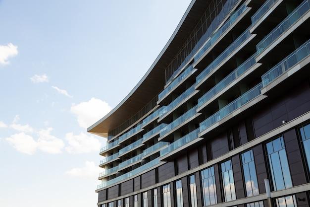 Zijaanzicht van fragment van moderne glazen gebouw met ramen en balkons bij daglicht