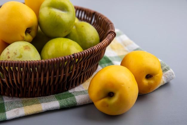 Zijaanzicht van fruit als groene plukken en nectacots in mand op geruite doek en op grijze achtergrond