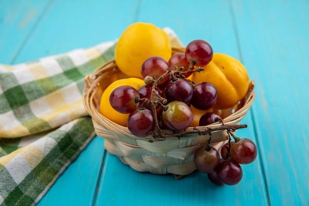 Zijaanzicht van fruit als nectacots en druivenmost in mand met geruite doek op blauwe achtergrond