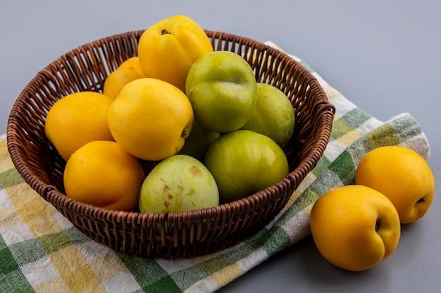 Zijaanzicht van fruit als nectacots groene pluots in mand en op geruite doek op grijze achtergrond