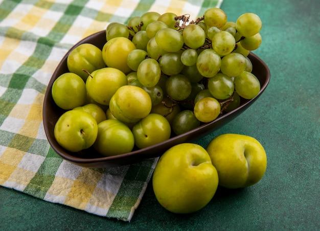 Zijaanzicht van fruit als pruimen en druivenmost in kom op geruite doek met groene plukken op groene achtergrond