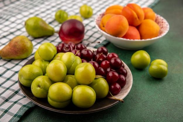 Zijaanzicht van fruit als pruimen, kersen, abrikozen in plaat en kom met peer en perzik op geruite doek op groene achtergrond