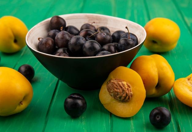 Zijaanzicht van fruit als sleedoornbessen in kom en abrikozen met half gesneden op groene achtergrond