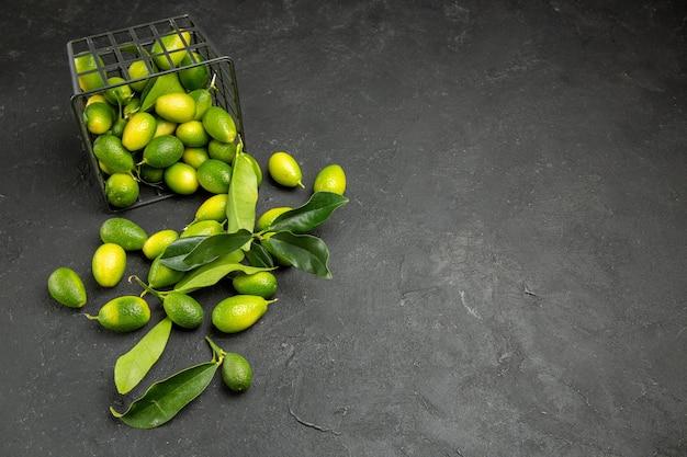 Zijaanzicht van fruit in de verte citrusvruchten met bladeren naast de mand met fruit