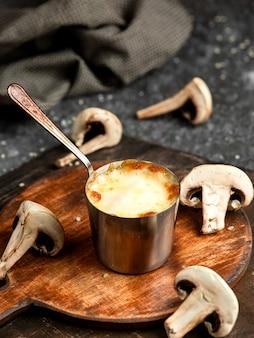 Zijaanzicht van gebakken champignon julienne met kip en kaas in een kleine kom op houten bord