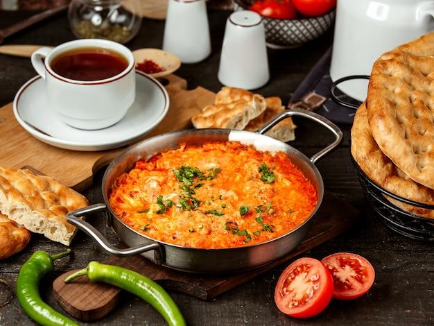 Zijaanzicht van gebakken eieren met tomaat in een pan