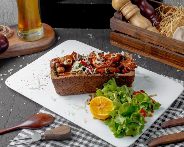 Zijaanzicht van gebakken inktvis en octopus met kaas en aardappelen ia een gesteund brood