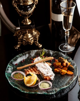 Zijaanzicht van gebakken visfilet gegarneerd met groenten kruiden en saus op een plaat met een glas witte wijn op tafel