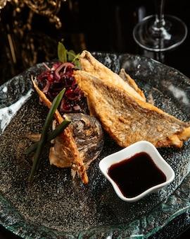Zijaanzicht van gebakken visfilet met rode uien en narsharab op een plaat