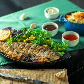 Zijaanzicht van gebakken zeebaars geserveerd met verse kruiden en sauzen op tafel