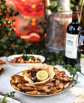Zijaanzicht van gebraden kip geserveerd met wijn op tafel