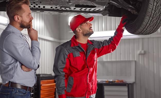 Zijaanzicht van geconcentreerde jonge zakenman in formele kleding en monteur in uniform controleren van details van kapotte auto in garage