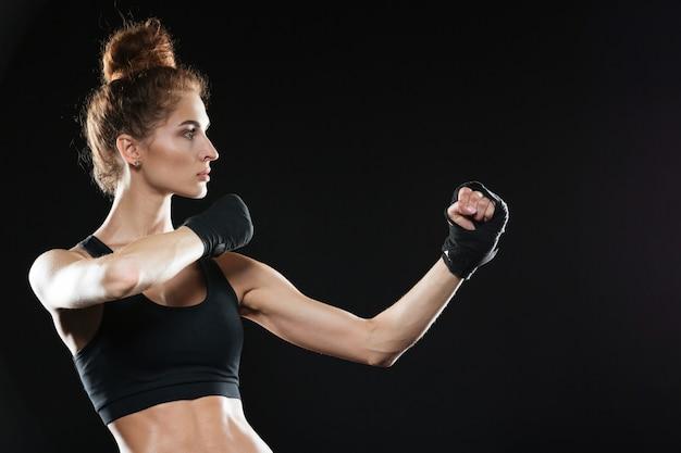 Zijaanzicht van geconcentreerde vrouwelijke vechter klaar om te vechten